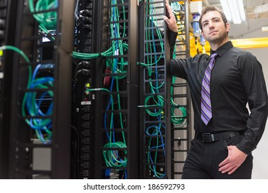A confident data center manager posing in front of the data center equipment racks.