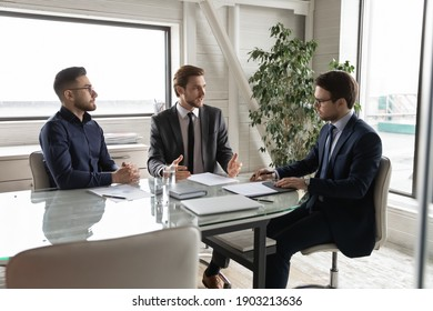 Confident diverse business partners discussing contract terms ro project strategy at meeting in boardroom, sitting at table, three businessmen talking, sharing ideas and opinions at briefing