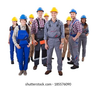 Confident diverse team of workmen and women standing grouped in their dungarees and hardhats smiling at the camera  high angle view isolated on white