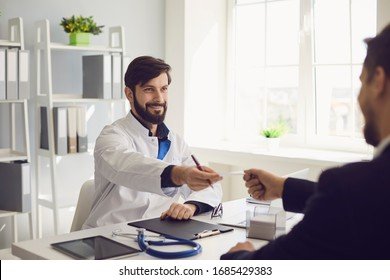 Confident doctor gives the patient a prescription while sitting at a table in a clinic office.