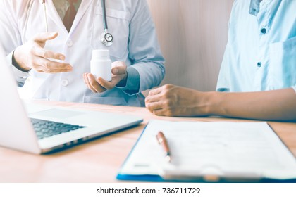 Confident doctor man holding a pill bottle while talking with a senior patient and reviewing his medication at office room.
