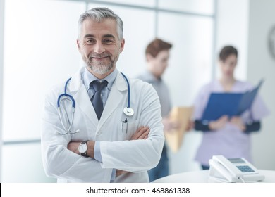 Confident doctor at the reception desk, he is posing with arms crossed and smiling at camera