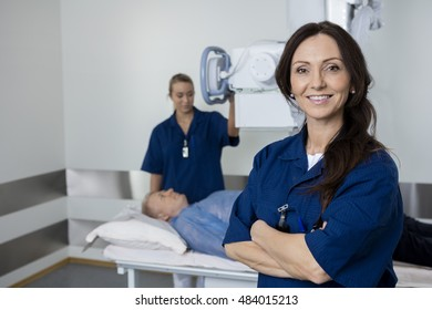 Confident Doctor Smiling While Colleague Taking Patient's Xray