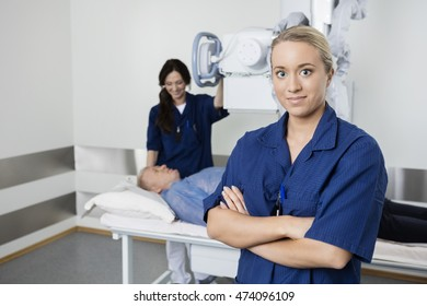Confident Doctor Smiling While Coworker Taking Patient's Xray