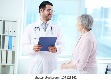 Confident doctor with stethoscope and clipboard interacting with his senior patient in hospital