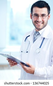 Confident doctor with stethoscope and clipboard looking at camera