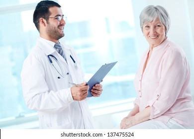 Confident doctor with stethoscope and clipboard speaking to his senior patient while she looking at camera