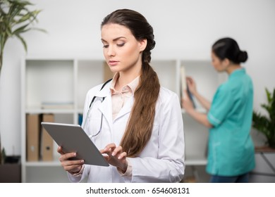 confident doctor wearing white coat and using digital tablet, internist standing behind in clinic