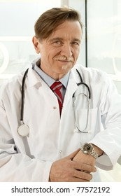 Confident doctor with white smock and stethoscope around the neck