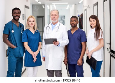 Confident doctor in white uniform and young doctors therapists posing looking at camera, elderly man holding clipboard in hospital, multidisciplinary medical team in white coats in aisle