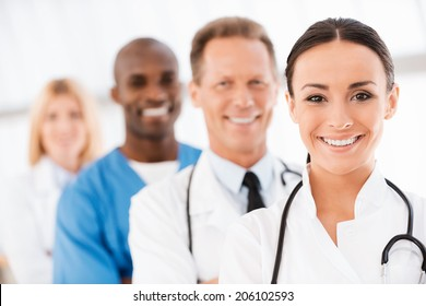 Confident doctors team. Confident female doctor looking at camera and smiling while her colleagues standing in a row behind her