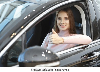Confident driver. Young cheerful beautiful woman sitting relaxed in a newly bought car at the car dealership showing thumbs up copyspace gesture symbol sign body language buying driver owner insurance
