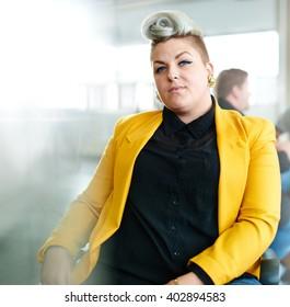 Zuversichtliche und edle Designerin, die an einem digitalen Tablett arbeitet, in rotem Kreativbüro