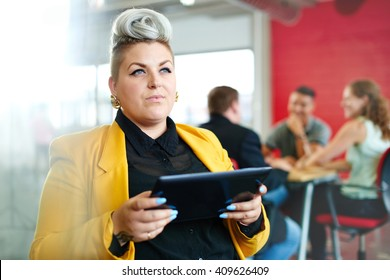 Confident and edgy female designer working on a digital tablet in red creative office space