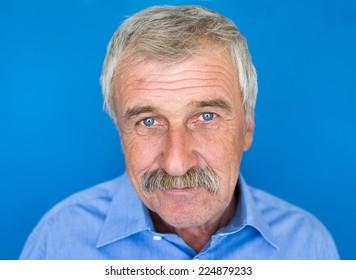 Confident elderly good looking man on blue wall
