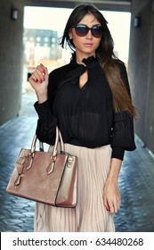 Confident, elegant woman dressed in a skirt with pleats and a black blouse, wearing sunglasses, holding the bag. Outdoor