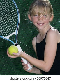 Confident Elementary Age Girl with Tennis Ball and Racket.
