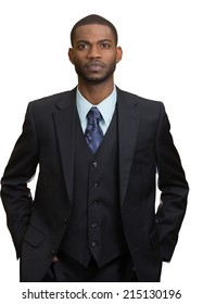 Confident employee. Closeup portrait Serious young business Man in full suit keeping arms in pockets, looking at camera, isolated white background. Human face expressions, emotions, body language