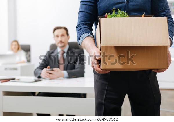 Dipendente fiducioso che lascia l'ufficio con le sue cose personali