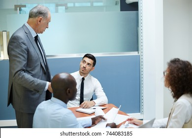 Confident employee talking to his director after business report at meeting