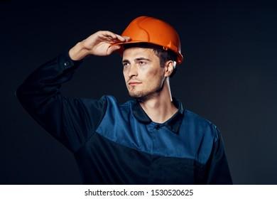 confident engineer in blue suit and orange helmet looks away risk