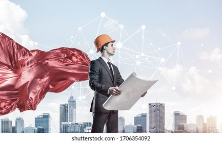 Confident engineer man in helmet and red cape against modern cityscape background
