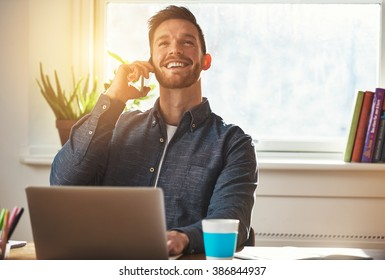 Confident entrepreneur chatting on a mobile phone while working at his desk looking up into the air with an elated smile of satisfaction