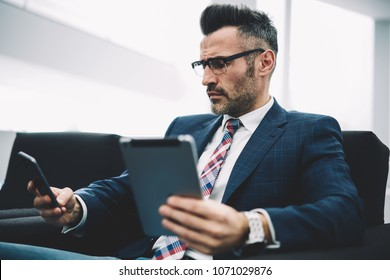 Confident entrepreneur in formal wear reading incoming sms message on smartphone while updating profile of banking account on modern touch pad device.Mature proud ceo sharing media via bluetooth