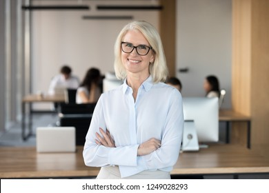 Confident executive manager middle aged female smiling looking at camera standing with crossed hands on chest in coworking space feels happy and satisfied. Team leader and successful employee concept
