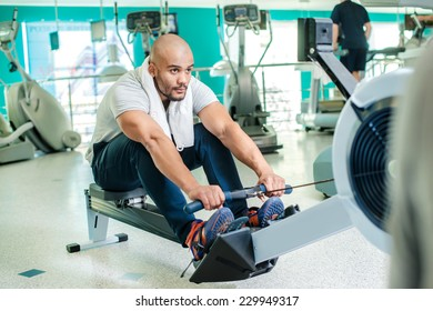 Confident exercise on rowing machine. Young man at the gym on rowing machine in full force.