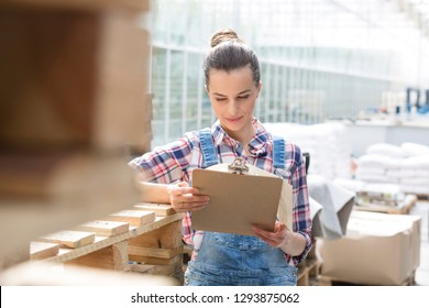 Confident farmer reading report on clipboard during distribution in greenhouse