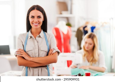 Confident fashion expert. Cheerful young woman keeping arms crossed and smiling while another woman sewing in the background