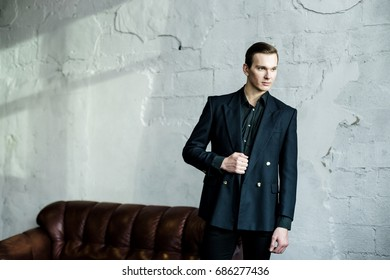 Confident fashionable young man in black shirt and jacket posing