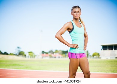 Confident female athlete standing with hand on hip on running track