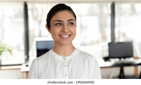 Confident female business leader posing in office, looking away, smiling. Head shot of Indian businesswoman thinking of new opportunities, planning goals, dreaming of future career. Close up portrait