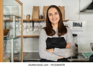 Confident female business owner standing at the counter of a restaurant with arms crossed, bakery waitress in apron looks at the camera and smiles