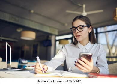 Confident female businesswoman noting contact of lawyer office searching professional to provide legal consultancy via smartphone connected to wireless network while waiting for meeting in coffee shop