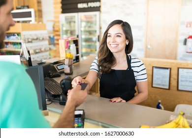 Confident female cashier receiving payment through credit card in supermarket