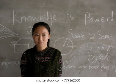 Confident female college students stand in front of the blackboard.