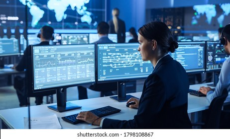 Confident Female Data Scientist Works on Personal Computer Wearing a Headset in Big Infrastructure Control and Monitoring Room. Woman Engineer in a Call Center Office Room with Colleagues.