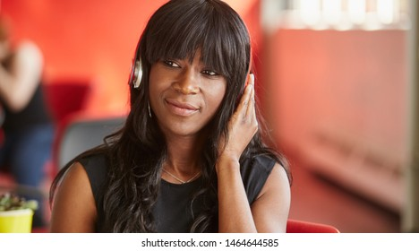 Confident female designer listening to music in red creative office space