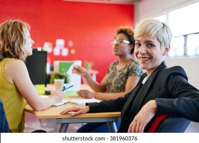 Confident female designer sitting at her desk for a brainstorming in red creative office space