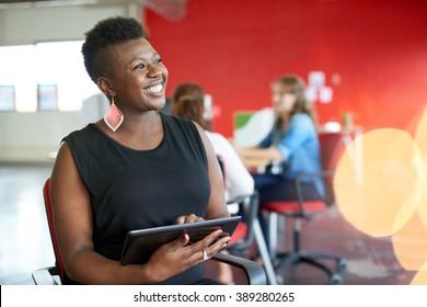 Zuversichtliche weibliche Designerin, die an einem digitalen Tablet in rotem Kreativbüro arbeitet