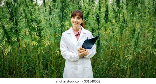 Confident female doctor with clipboard posing in a hemp field, alternative herbal medicine concept
