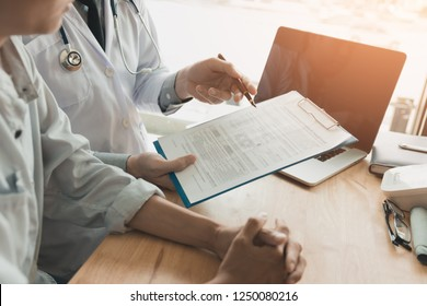 Confident female doctor reviews patient medical information and pointing to medical forms.