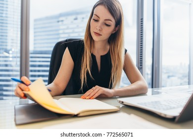 Confident female entrepreneur planning her workday sitting at her desk holding pen thinking looking at notebook in office