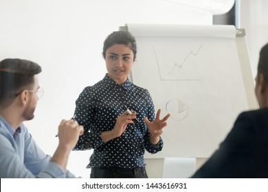 Confident female indian conference speaker coach training diverse employees group give flip chart presentation at office meeting, hindu business woman presenter teach staff team at corporate workshop