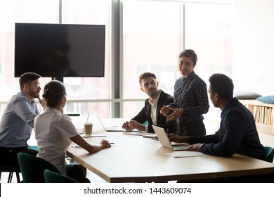 Confident female indian manager company worker lead diverse employees group meeting in conference room, hindu business woman team leader presenting work plan at corporate briefing at boardroom table