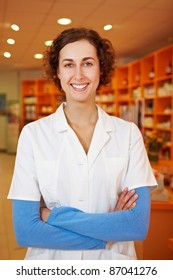 Confident female pharmacist with arms crossed in her pharmacy