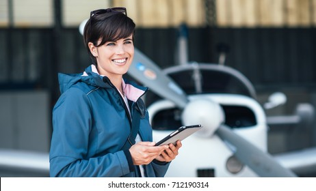 Confident female pilot in the hangar preparing before departure, she is using aviation apps on her tablet and smiling at camera, light aircraft on the background